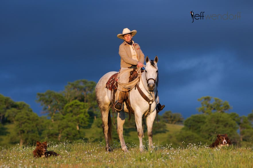 Cowboy on her horse with a stormy sky photographed by Jeff Wendorff